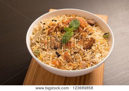 Yummy delicious chicken biryani in a white round bowl