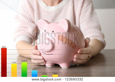 Business accounting concept. Woman holding Piggy Bank with adhesive bandage