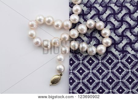 Overhead photo of pearl necklace on white background and blue and white indigo cloth