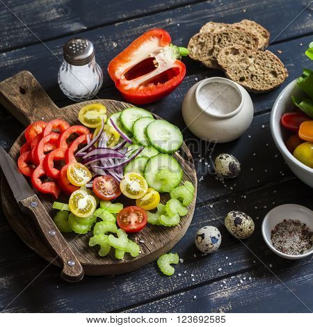 Ingredients to prepare vegetable salad - tomatoes cucumber celery bell pepper red onion quail eggs garden herbs and spices on a rustic wooden board. Healthy food
