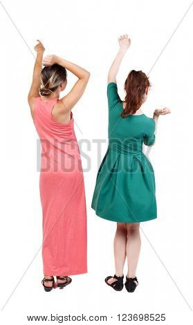 Back view of two young  women dancing.  Rear view people collection.  backside view of person.  Isolated over white background. Two girls in dresses in a disco.