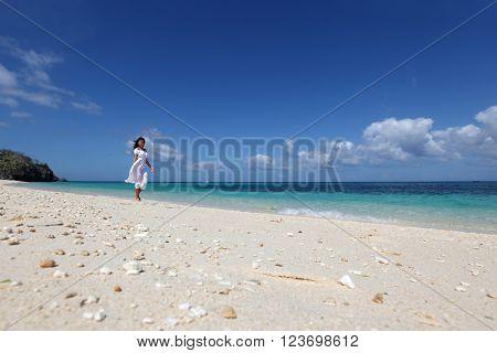 Beautiful young woman in white dress walking on beach