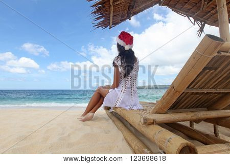Woman in Santa Claus hat sitting at chaise lounge with straw parasol on white sandy beach at Philippines