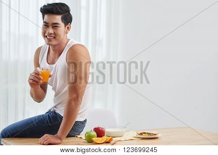 Cheerful handsome Vietnamese man drinking fruit juice in the morning