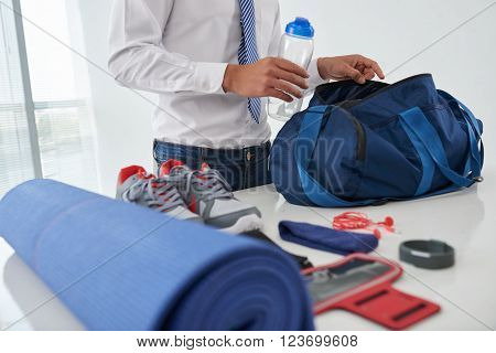 Cropped image of businessman preparing gym bag at home