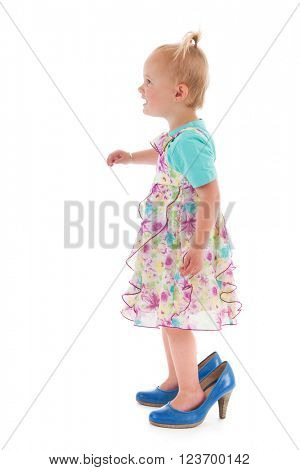 Toddler girl standing inmothers big shoes isolated over white background