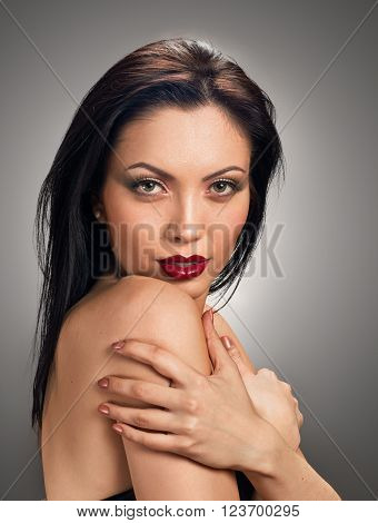 Pretty model. Beautiful Professional Makeup. Red Lips. grey background
