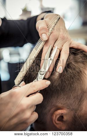Close up of beautician's hand giving a haircut to male customer at parlor. Professional hairdresser tools ** Note: Visible grain at 100%, best at smaller sizes