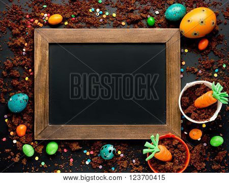 Beautiful colorful Easter sweet food background: traditional holiday baking treat dessert eggs candy chocolate biscuit cookie crumbs and sprinkling on black blank space for text on chalkboard top view
