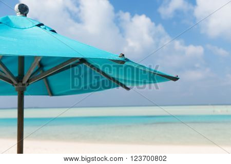 travel, tourism, vacation, beach and summer holidays concept - parasol over blue sky and beach