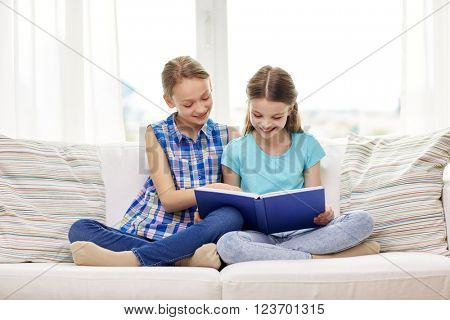 people, children, friends, literature and friendship concept - two happy girls sitting on sofa and reading book at home