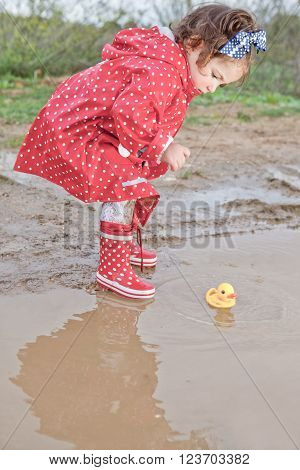 Baby girl dressed with dotted raincoat and rainboots playing with her water toys on muddly puddles