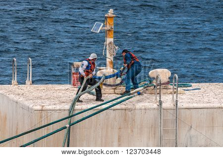 Puerto Madryn Argentina - December 13 2012: On the mooring platform a workers casts off the mooring cable of a ship in harbor of Puerto Madryn Patagonia Argentina South America