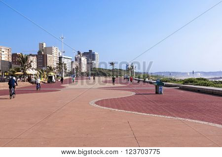 DURBAN SOUTH AFRICA - MARCH 23 2016: Many unknown people walk and cycle along paved promenade against city skyline in Durban South Africa