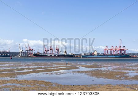 DURBAN SOUTH AFRICA - MARCH 23 2016: Four unknown people and container ships moored in harbor at low tide in Durban South Africa