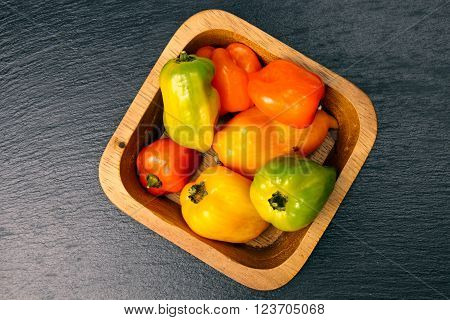 A wooden bowl of Habanero peppers on grey stone background with copy space.