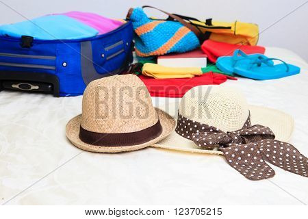 two hats and suitcase with clothing on bed in room, packing and travel