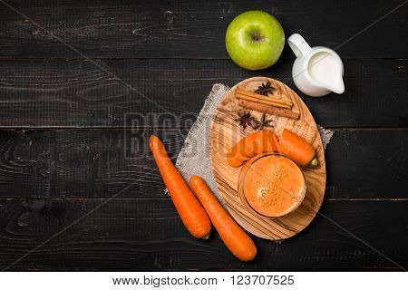 Glass of carrot juice and carrots on black wooden background, top view