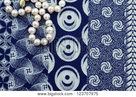 Pearl necklace on indigo cloth background isolated