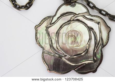 Close up of mother of pearl chain and pendant isolated on white background