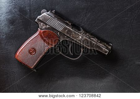 Weathered generic russian soviet semi-automatic 9mm pistol on black leather background