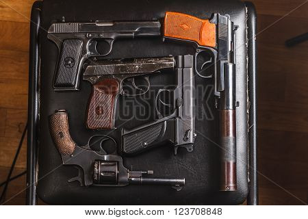 Weathered generic russian soviet semi-automatic 9mm pistols on black chair