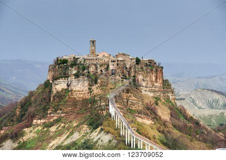 Civita di Bagnoregio, it is a small town in the Province of Viterbo in Italy. The town is famous for its position atop a plateau of friable volcanic tuff overlooking the Tiber river vally.