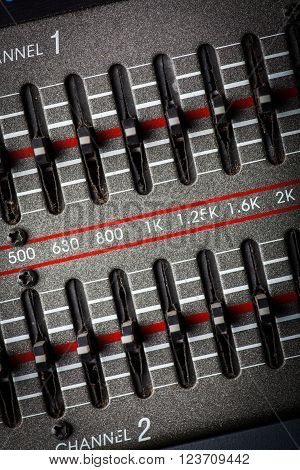 Color image of many buttons on a sound mixer in a recording studio.