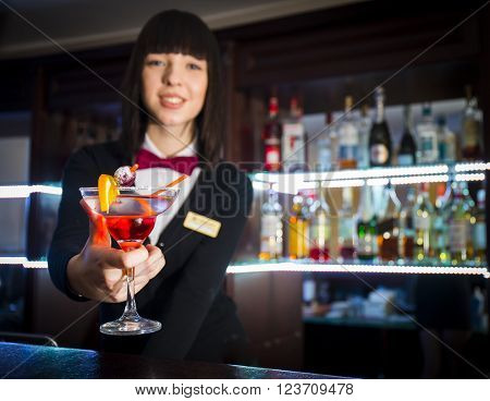 Bartender girl at night club counter offering coctail