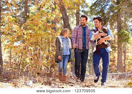 Gay Male Couple With Children Walking Through Fall Woodland