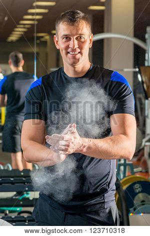 Happy Weight Lifter In The Gym Preparing Arms Against Sliding