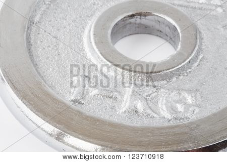 Metal round weight of one kg closeup in silver