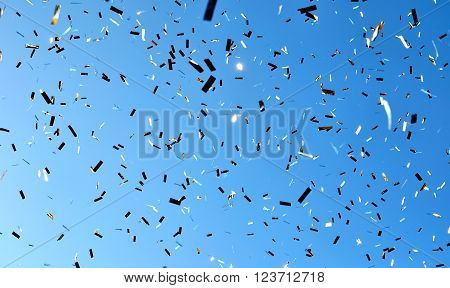 falling confetti in the city festival on blue sky background
