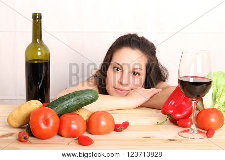 A young woman cutting vegetables ion the kitchen.