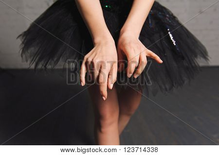 Close-up. hands ballerina on a background of black tutu. Graceful movements of hand. ballerina hands touched to the ballet skirt, dress.