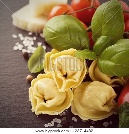 Homemade raw Italian tortellini filled with ham and cheese with raw tomatoes, basil leaves and cheese on black background. Healthy food concept. Selective focus. Toned photo.