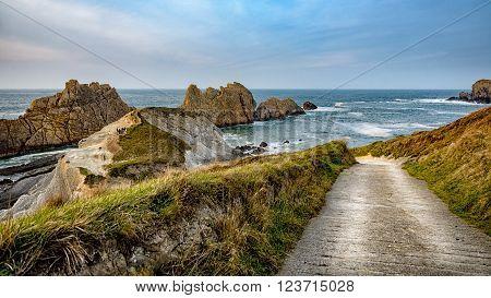 Small road towards the rocky coast and islets