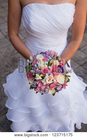 round bouquet with white roses, purple and pink freesia and pearls in the hands of the bride. The bride wore a bustier dress.