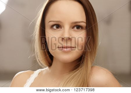 Closeup portrait of pure young woman looking away.