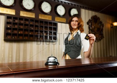 Modern hotel reception counter desk with bell. Hotel receptionist gives a card to a guest. Woman receptionist at desk unfocused. Selective focus at counter bell. Travel, hospitality concept.