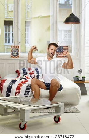 Young man yawning and stretching on bed in the morning eyes closed.