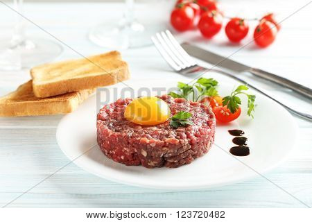 Beef Tartare With Egg Yolk On A Blue Wooden Table