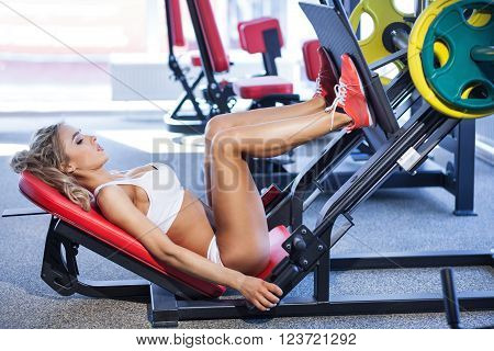 Sportive blonde using weights machine for legs at the gym