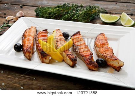 Restaurant food, salmon dish. Hot fish dish. Barbecue grilled fish dish. Restaurant food catering. Salmon barbecue grill roasted with lemon and olives. Grilled salmon served in restaurant closeup.