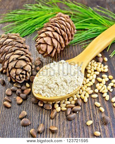 Cedar Flour in a wooden spoon, cedar nuts and  two cones, cedar branch against the backdrop of wooden planks