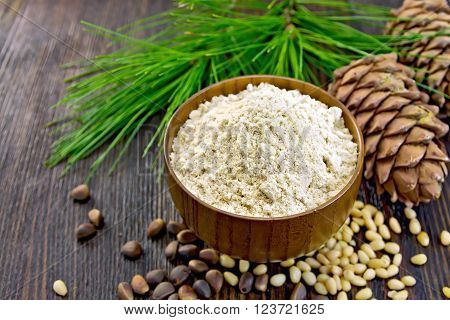 Flour cedar in a wooden bowl, cedar nuts and  two cones, cedar branch with green needles on the background of wooden boards