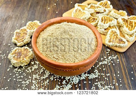 Sesame flour in a clay bowl and homemade cookies on a wooden boards background
