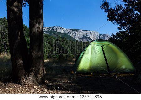 Iluminated tent against mountain at moon night