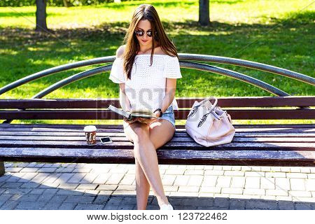 Beautiful girl student with glasses and a bag of coffee, sitting on a park bench, reading a book, fashion style, school life, in the summer on a sunny day in the fresh air. Schoolgirl resting.