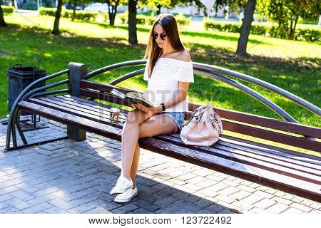Beautiful girl student with glasses and a bag of coffee, sitting on a park bench, reading a book, fashion style, school life, in the summer on a sunny day in the fresh air.